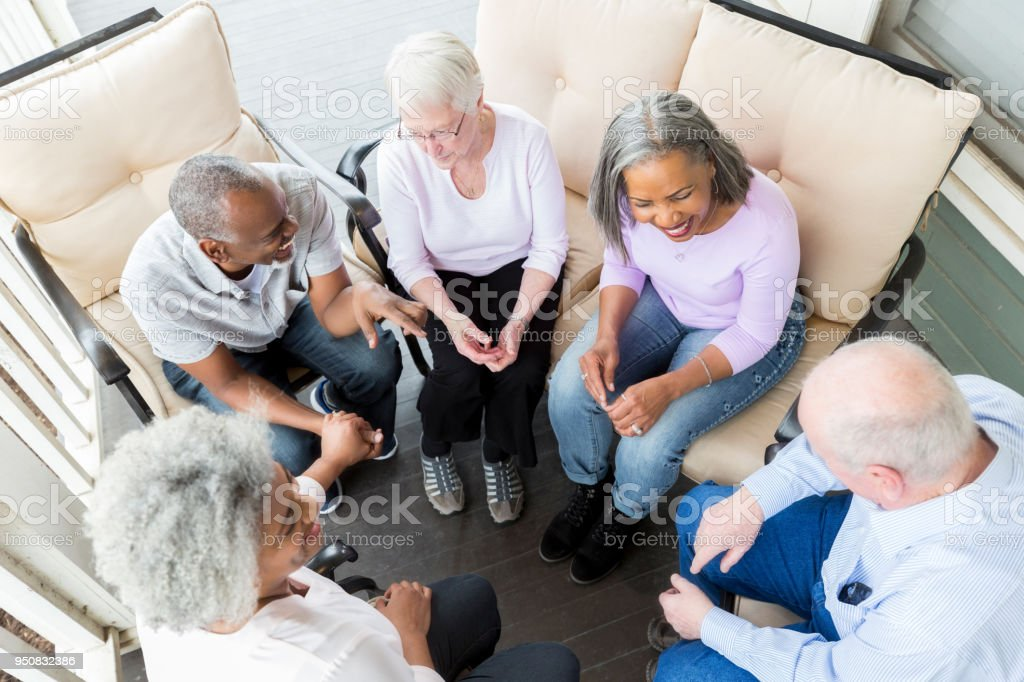 Group of seniors enjoy discussing something while sitting on the...