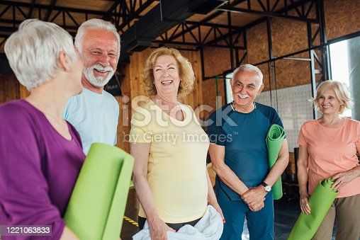 1047537292 istock photo Group of seniors laughing and having fun before yoga class 1221063833