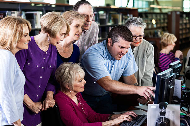 Group of Seniors Learn About Computer in Library stock photo