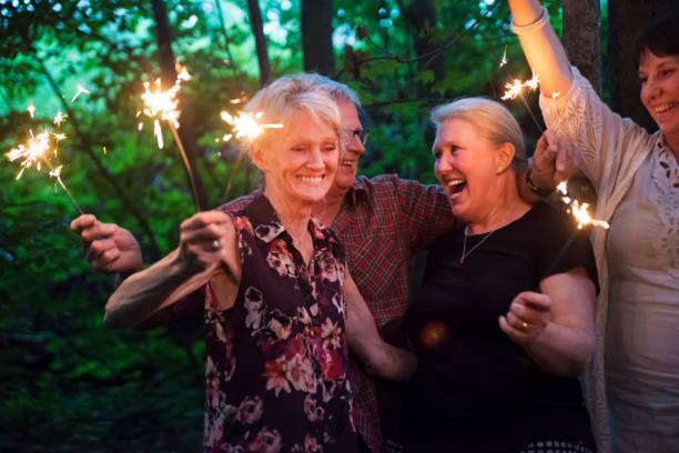 Gruppe von Senioren, die Beleuchtung Wunderkerzen in der Natur in der Abenddämmerung. – Foto