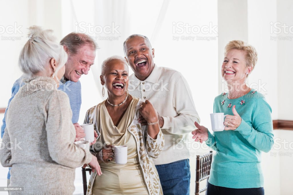 Group of seniors socializing over coffee stock photo