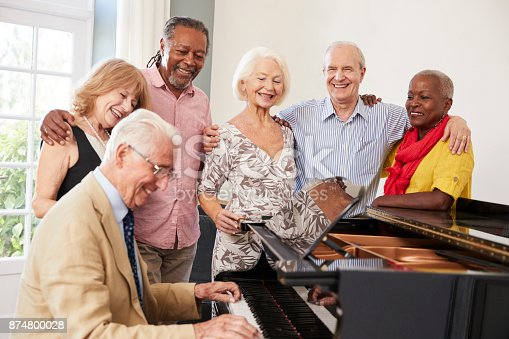 istock Group Of Seniors Standing By Piano And Singing Together 874800028
