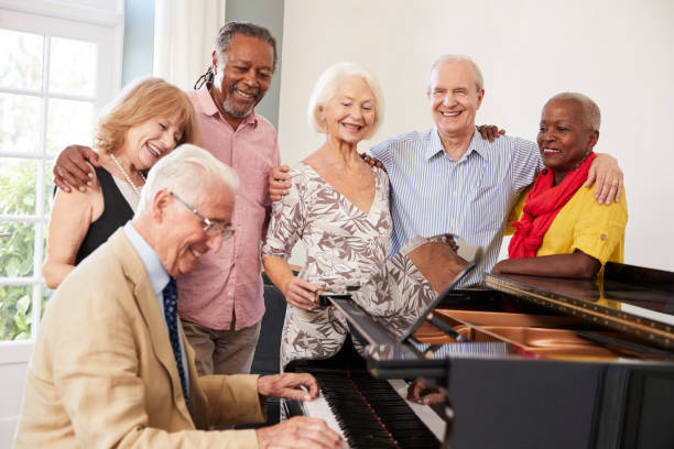 group of seniors standing by piano and singing together - elderly group stock photos and pictures