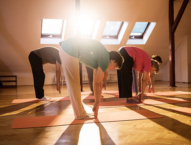 Group of seniors stretching to touch toes. Group of seniors exercising in a health club and trying to touch their toes. touching toes stock pictures, royalty-free photos & images