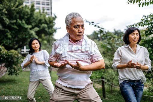 Group of three seniors taking an exercise class in the park, practicing tai chi, standing with their hands raised