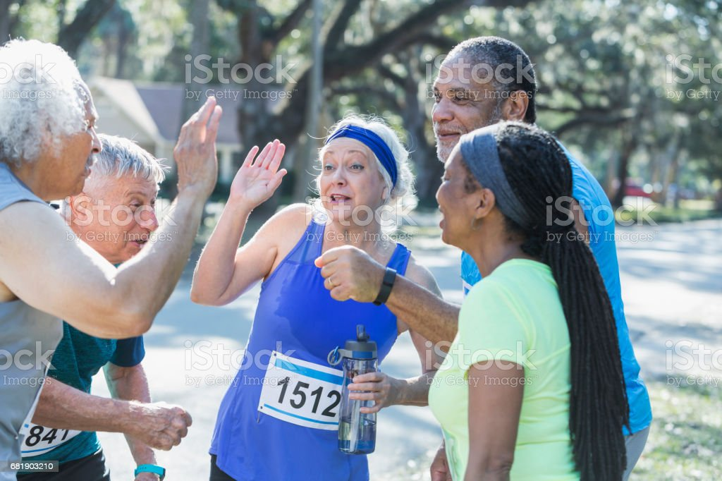 Group of seniors talking at end of race, high fives stock photo