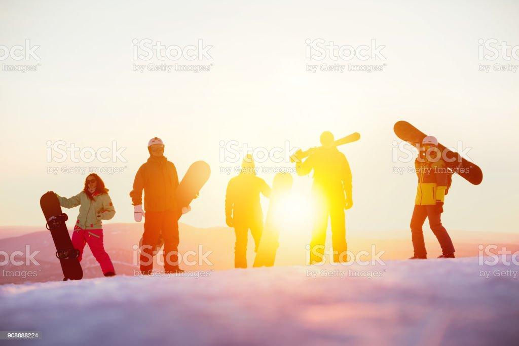 Grupo de amigos serios con ski y snowboards contra puesta de sol - foto de stock