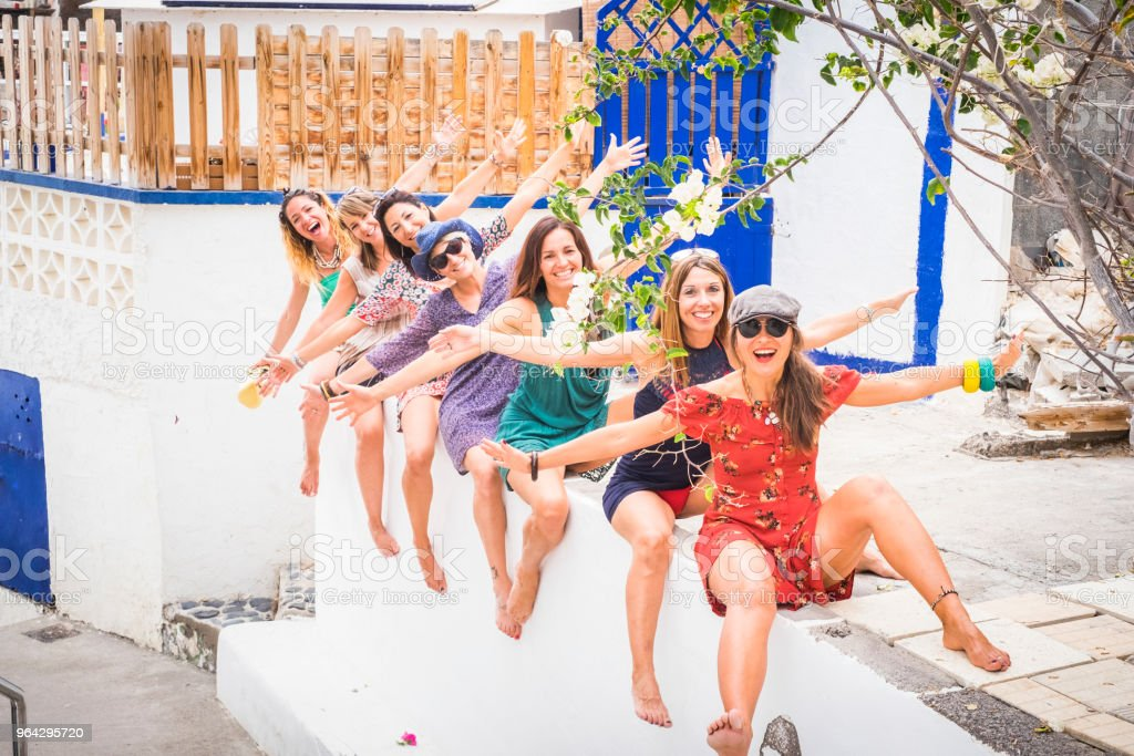group of seven young smile beautiful woman crazy in vacation and friendship or relationship stay together sit down and go crazy with laugh. summer colors and bright image for joy concept stock photo