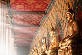 Close up shiny golden buddha statues in a row with beam of light in buddhist temple, Wat Arun in Bangkok, Thailand