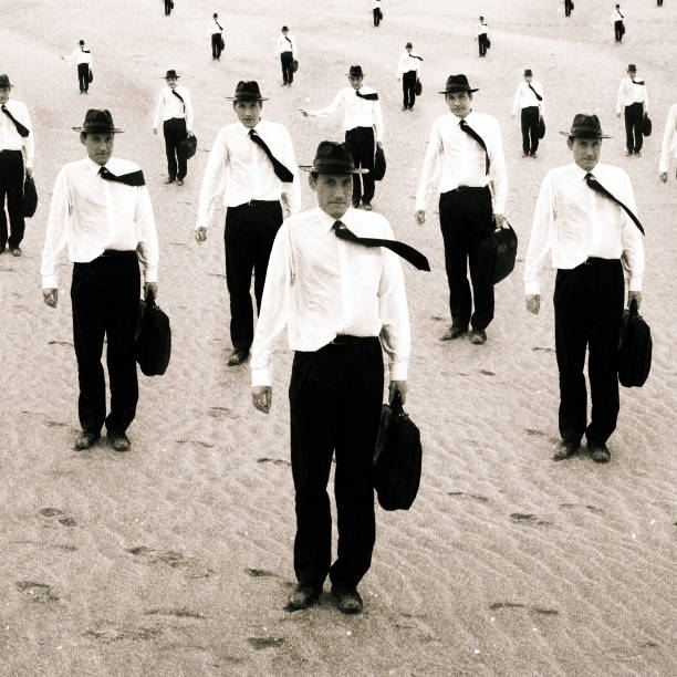 Group of Similiar Men Standing on Sand stock photo