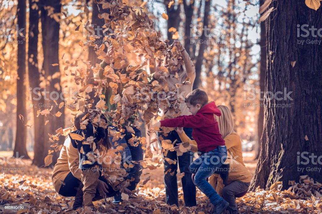 Group of single parents playing with leaves with children in park stock photo