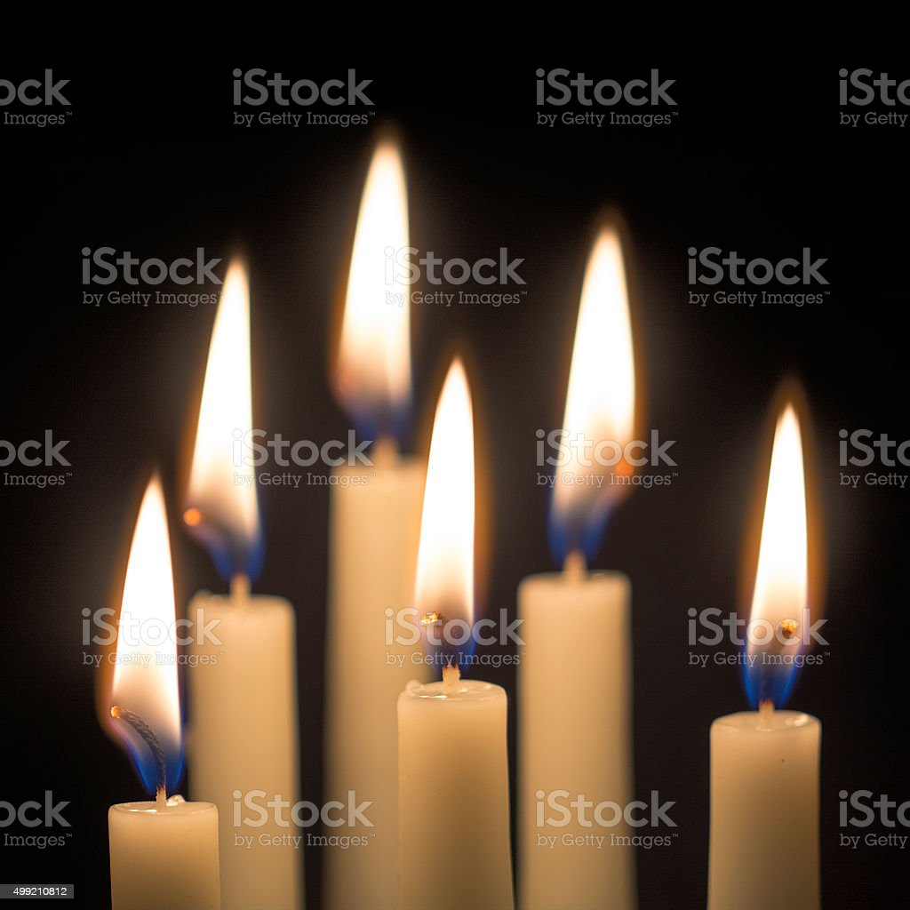group of six burning candles against black background, selected stock photo