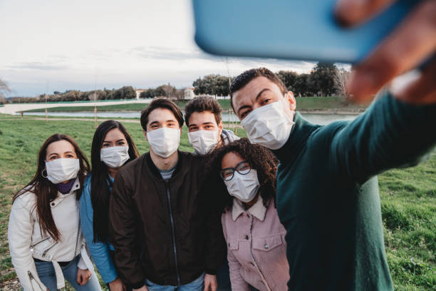 Group of six friends taking a selfie together while they are wearing protecting masks stock photo
