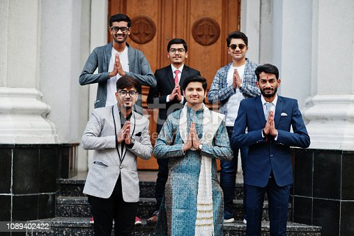 Group of six south asian indian mans in traditional, casual and business wear standing on stairs and show namaste hands sign.