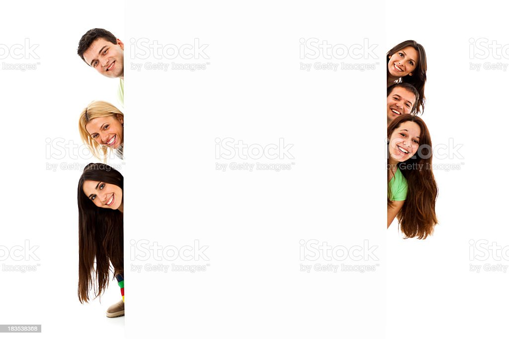 Group of six young people peeking behind blank banner sign stock photo