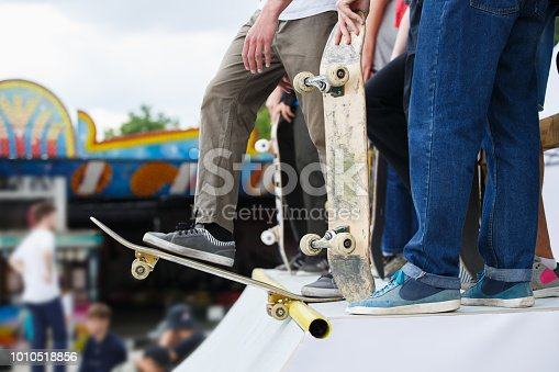 Group of teenager skater boys riding on skateboards in skatepark at competition.Summer extreme sports background.Popular youth activity.Focus on athletes feet on board