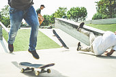 Group of skaters friends performing trick in pubblic park - Young men training with skateboards - Extreme sport, youth lifestyle concept- Focus on behind guy face