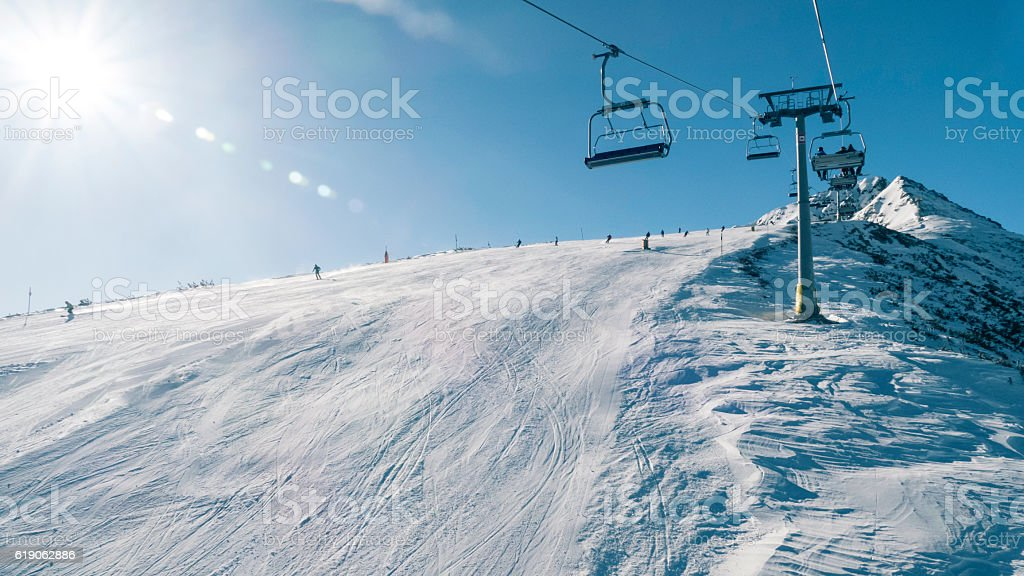 Group of skiers moving down on ski slope stock photo