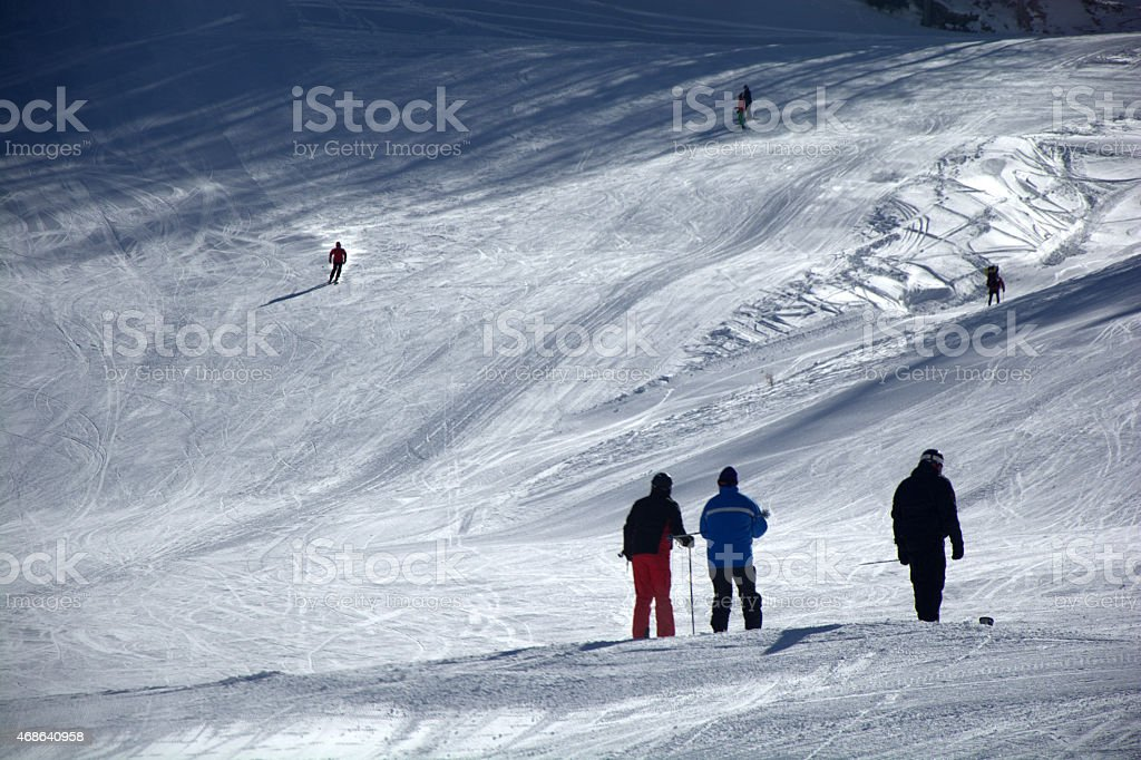 group of skiers on a ski slope in the alps stock photo