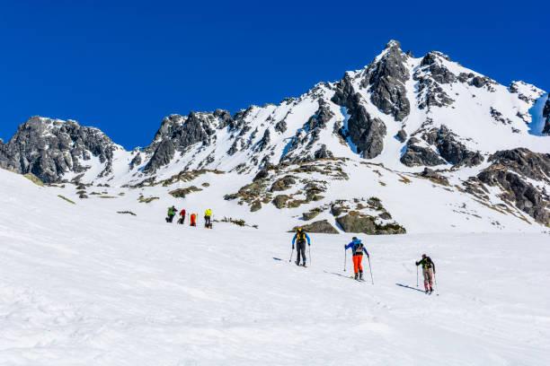 Eine Gruppe von Skifahrern (Freeriden) auf einer Reise durch das Tal. Ein schöner sonniger Tag, perfekt für die Bewunderung der umliegenden Gipfel. – Foto