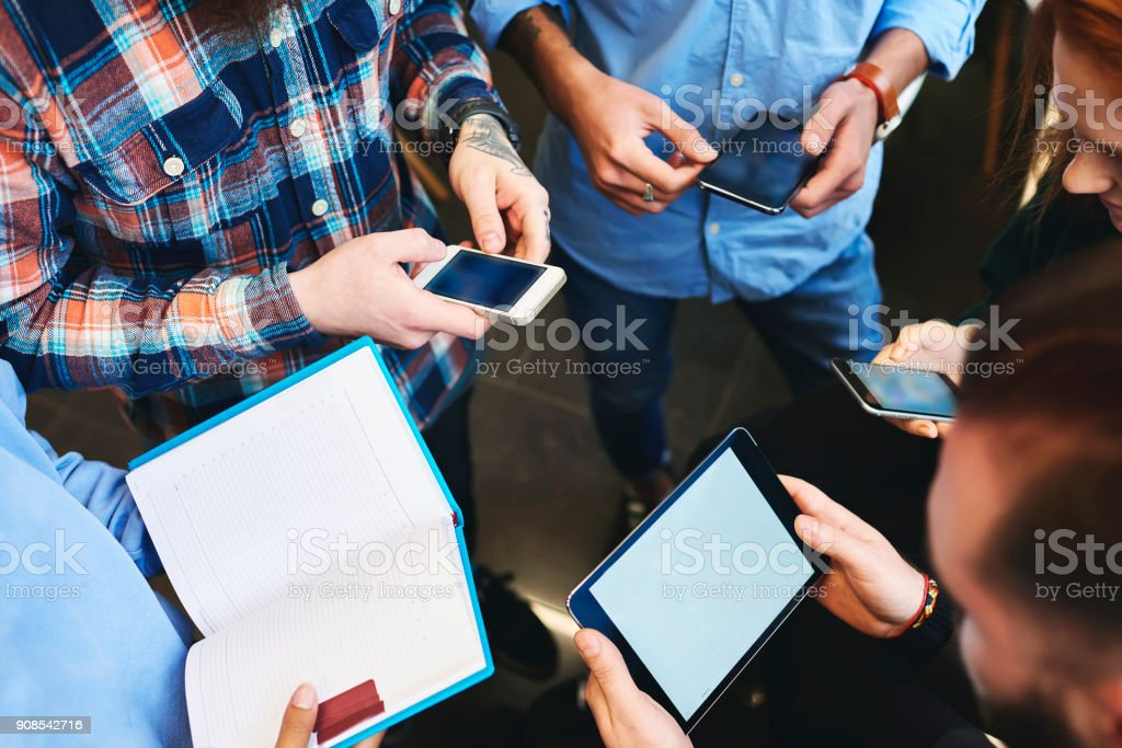 Group of skilled young male and female IT developers testing new software for digital devices using gadgets connected to free wireless internet in office while discussing advantages and disadvantages stock photo