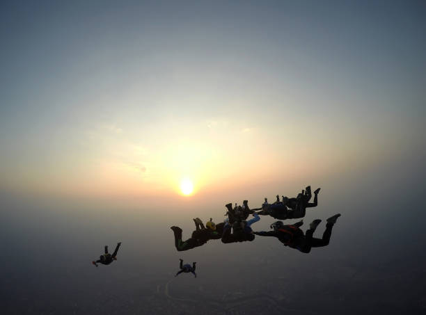 A group of skydivers perform a jump at sunset. stock photo