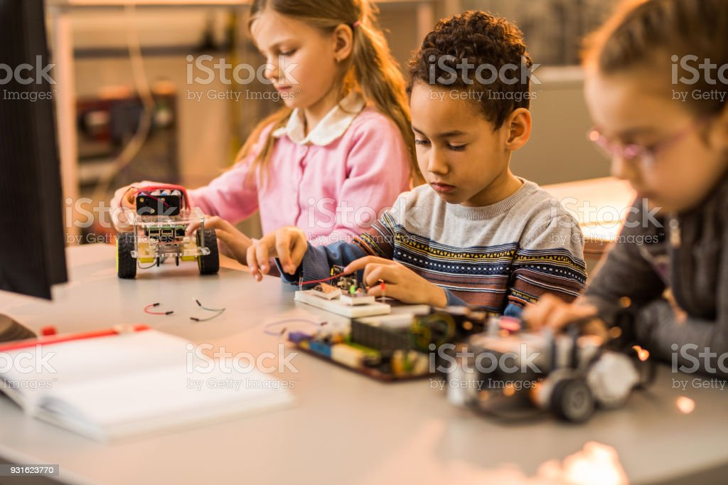 African American boy assembling electrical components of futuristic...