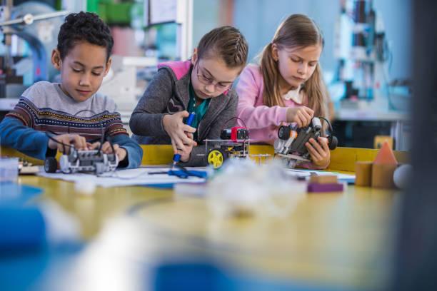 Groupe de petits ingénieurs travaillant sur des robots innovants en laboratoire de l'école. - Photo