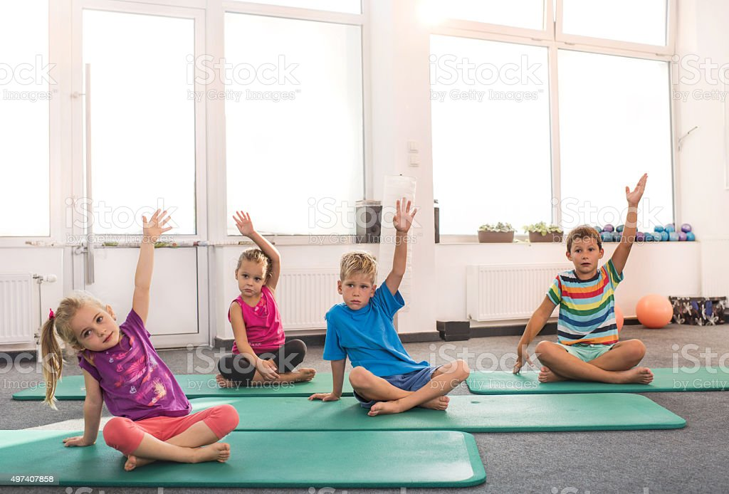 Small children sitting on exercise mats in a gym and doing relaxation...