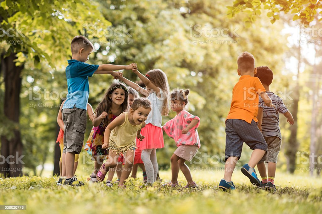 Group of small kids having fun while playing in nature.
