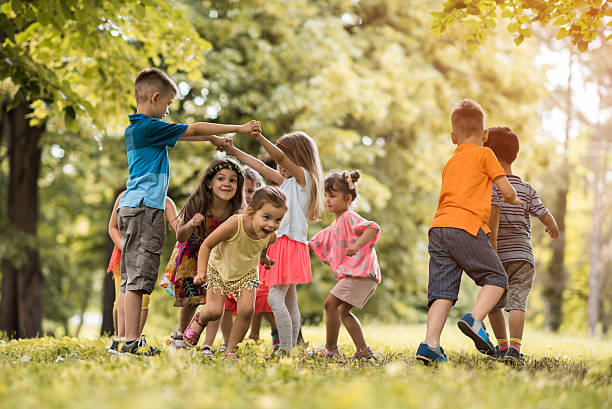 Group of small kids having fun while playing in nature. stock photo
