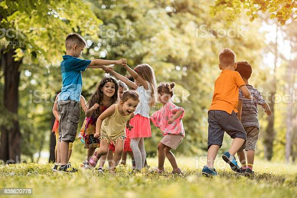 Group of happy little children having fun in the park.