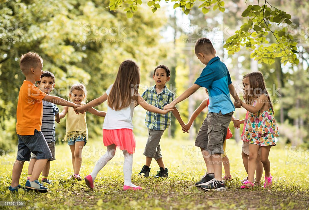 Group of small kids playing ring-around-the-rosy in the park. - Photo
