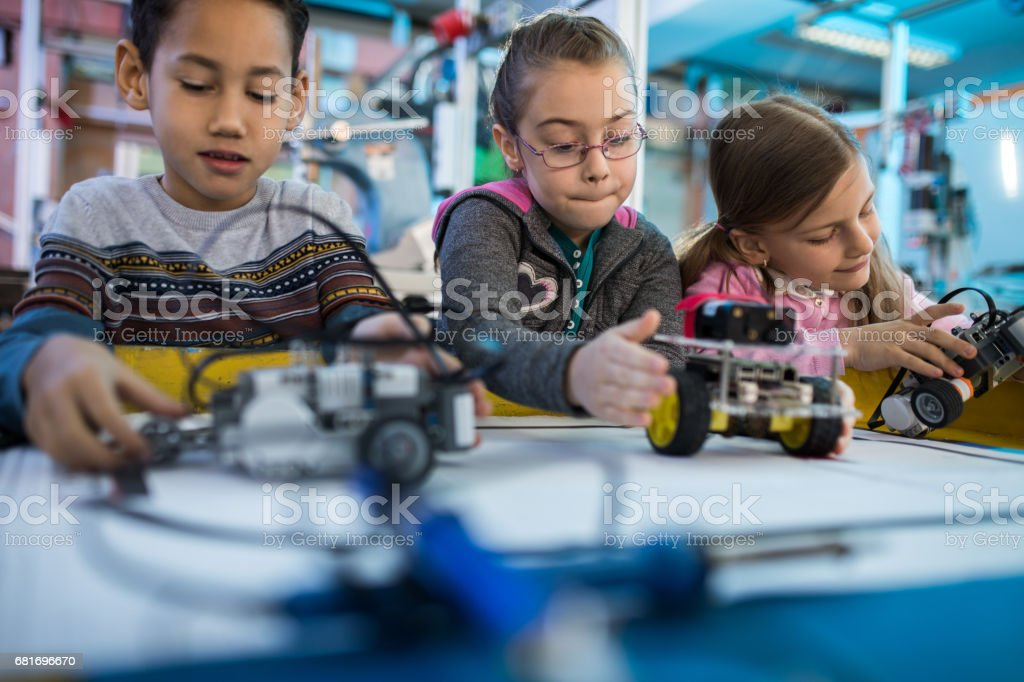 Group of small kids working on robots on a robotics class. stock photo