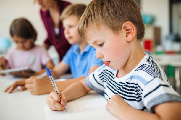 A group of small school kids with teacher in class writing. stock photo