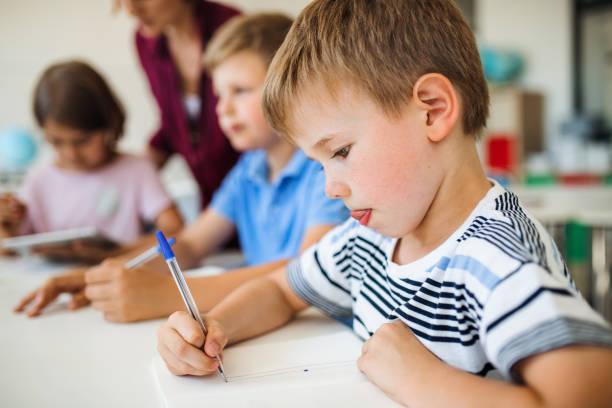 un groupe de petits enfants d'école avec l'enseignant dans l'écriture de classe. - enfance photos et images de collection