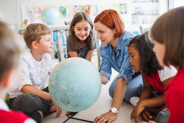 um grupo de miúdos da escola pequena com o professor que senta-se no assoalho na classe, aprendendo. - infância - fotografias e filmes do acervo