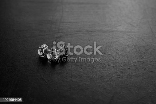 istock Group of small screws on the black background. 1204984406