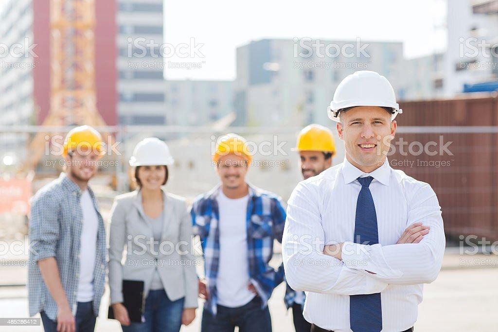Gruppe von lächelnden builders in hardhats im Freien - Lizenzfrei 2015 Stock-Foto