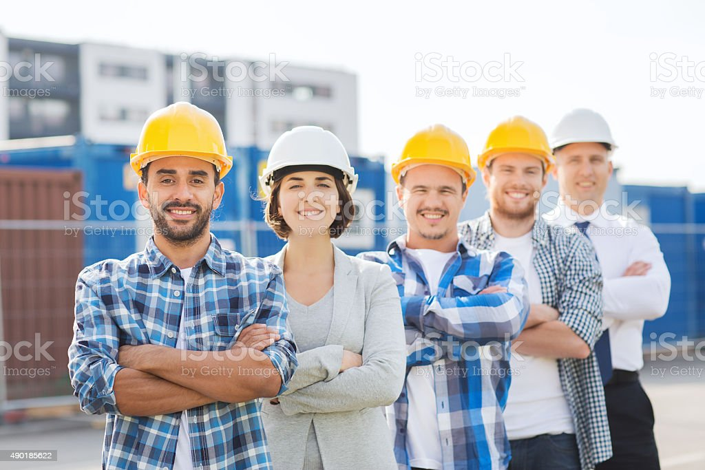 group of smiling builders in hardhats outdoors stock photo