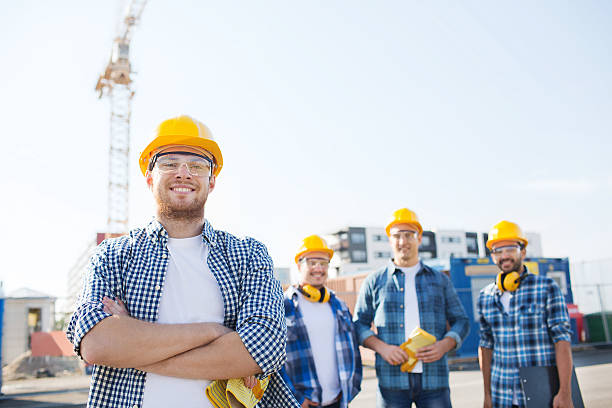 group of smiling builders in hardhats outdoors - builders stock photos and pictures