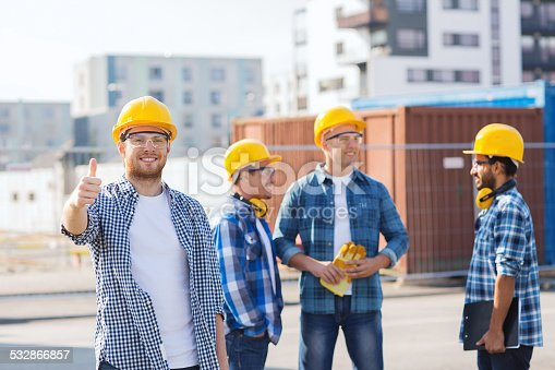 488715470istockphoto group of smiling builders in hardhats outdoors 532866857