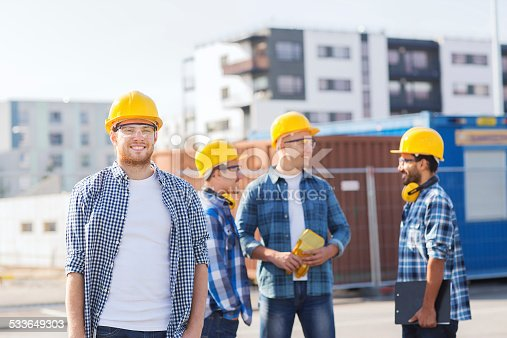 488715470istockphoto group of smiling builders in hardhats outdoors 533649303