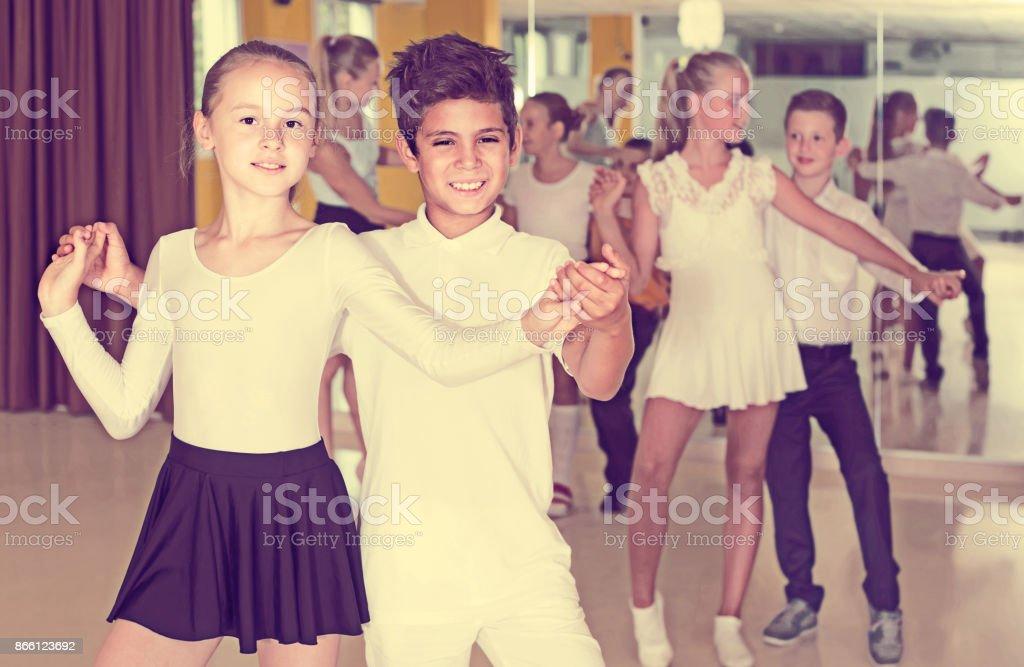 Group of smiling children dancing salsa in school stock photo