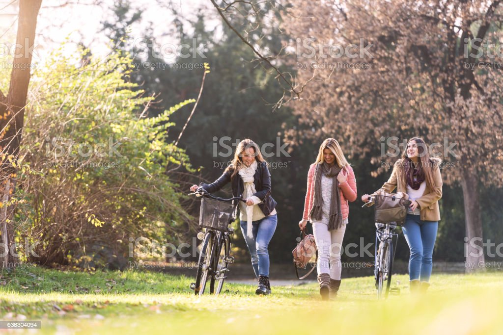Group of smiling college girls walking in the park stock photo