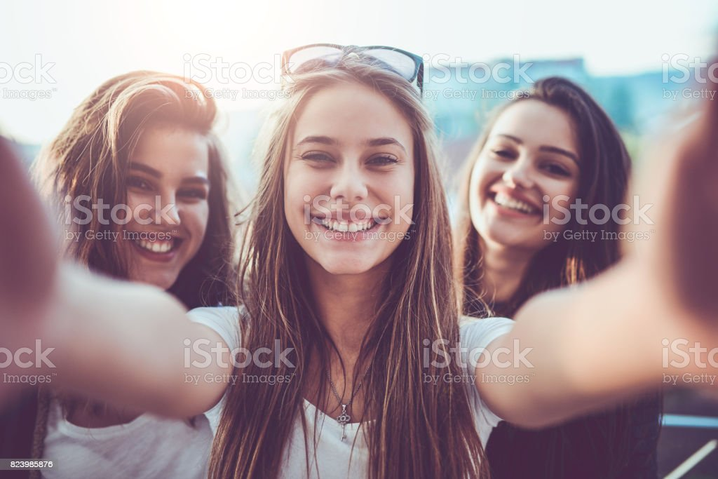Group of Smiling Crazy Girls Taking Selfie and Making Faces Outdoors stock photo