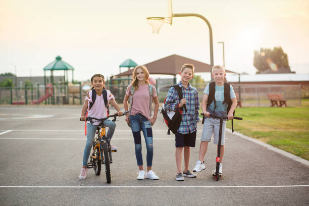 Group of smiling elementary school students on their way home stock photo