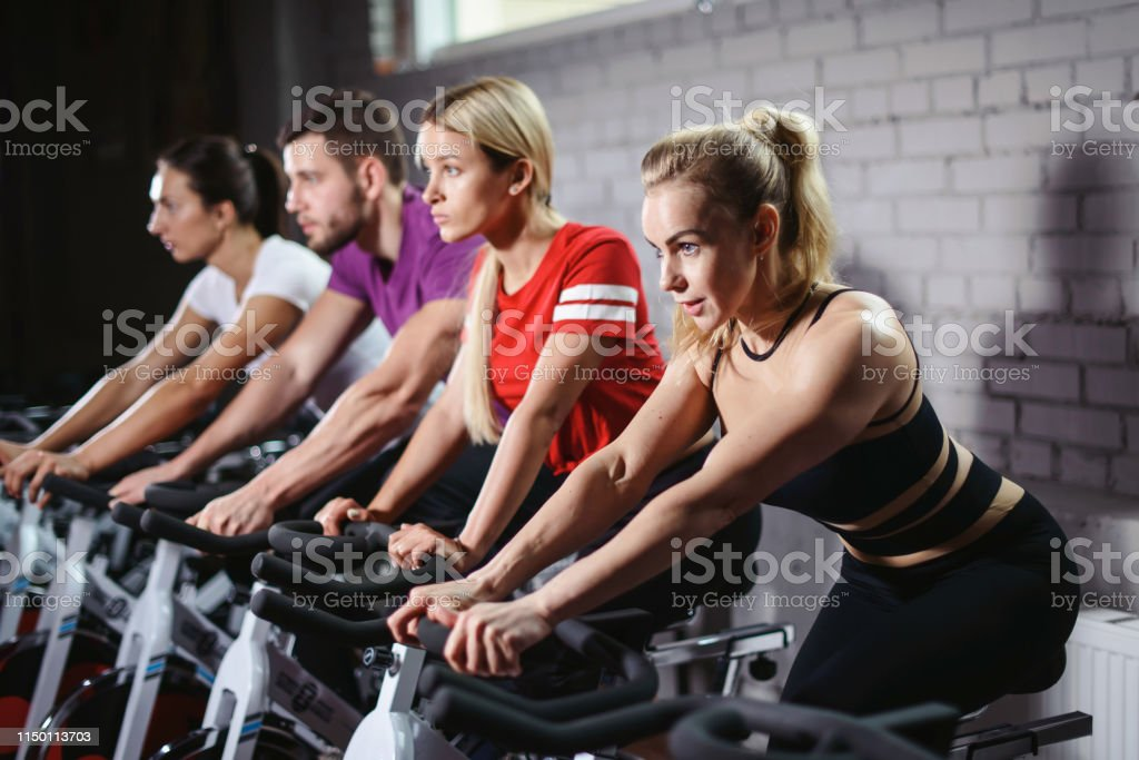 Group of smiling friends at gym exercising on stationary bike. Happy...