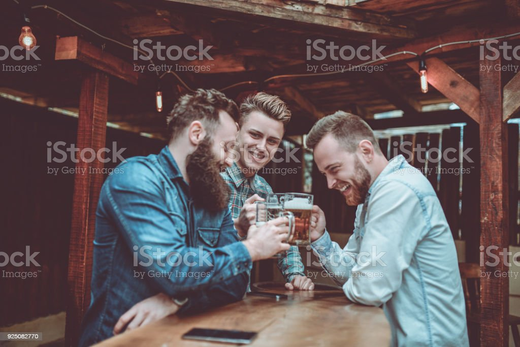 Group of Smiling Friends Celebrating with Beer stock photo
