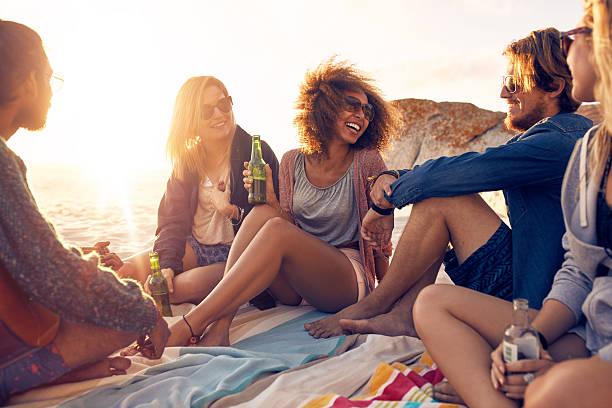 group of smiling friends chilling on the beach - strandfeest stockfoto's en -beelden